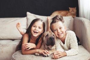 zwei mädchen mit shar pei hund und katze auf einem sofa