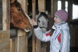 Mädchen mit zwei Pferden im Stall