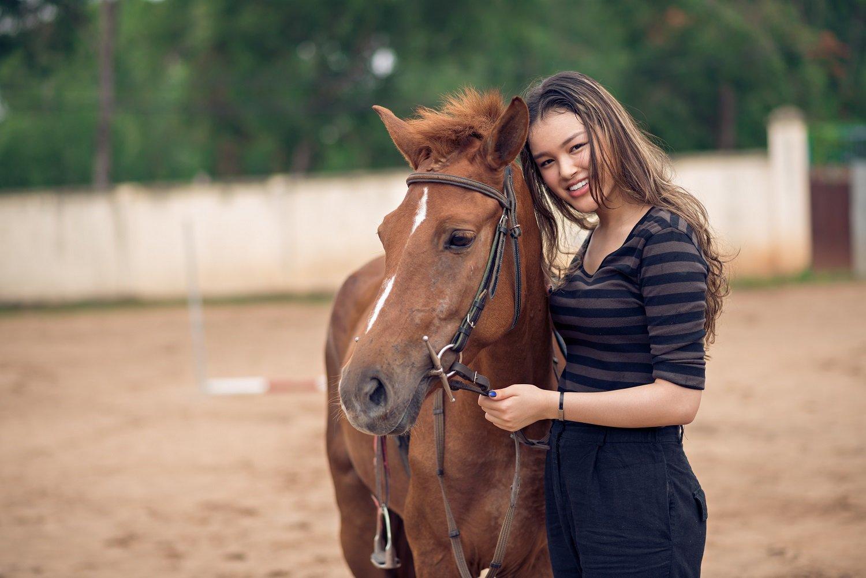 Glückliche Besitzerin neben eigenem Pferd